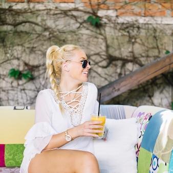 Het glimlachen van de zitting van de blonde jonge vrouw op het glas die van de bankholding sap weg eruit zien