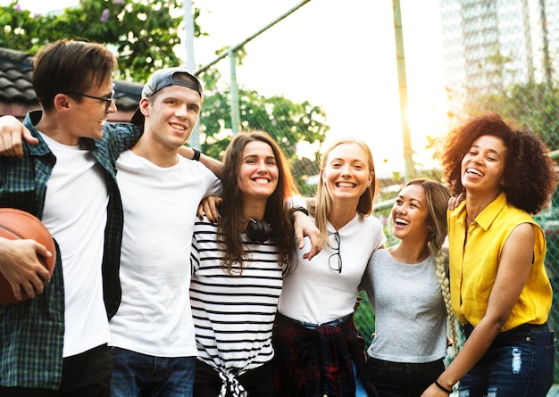 Het glimlachen van gelukkige jonge volwassen vrienden bewapent rond schouder in openlucht vriendschap en verbindingsconcept