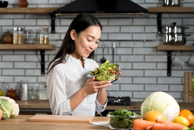 Het glimlachen van het glas van de vrouwenholding kom met salade