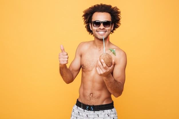 Het glimlachen van jonge afrikaanse mens het drinken cocktail en het tonen van duimen.