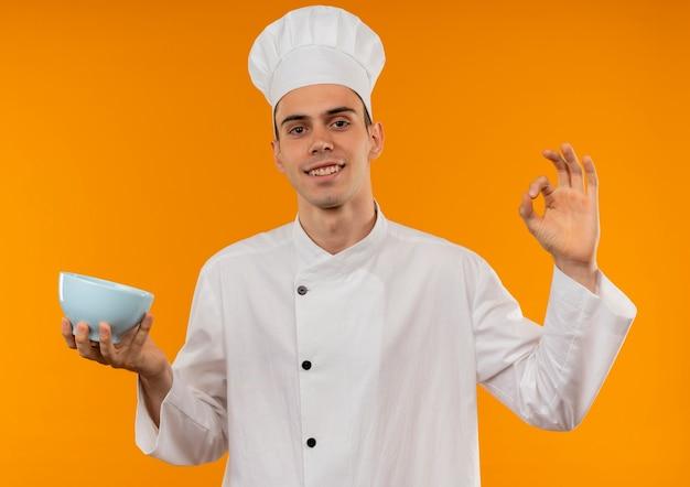 Het glimlachen van jonge mannelijke koele dragende kom die van de chef-kok eenvormige holding okgebaar tonen