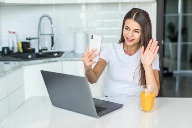 Het glimlachen van jonge vrouwenvideo die telefoon in keuken uitnodigen