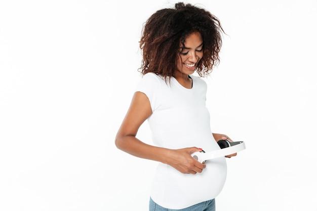 Het glimlachen van jonge zwangere afrikaanse vrouw het luisteren muziek met hoofdtelefoons.
