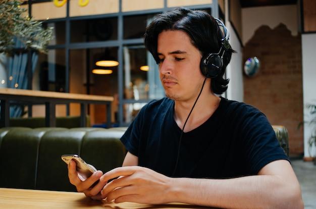 Het glimlachen van jongen het luisteren muziek met hoofdtelefoons in een koffiewinkel