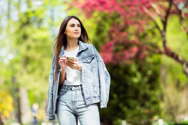 Het glimlachen van kaukasische donkerbruine jonge vrouw die bericht op smartphone verzenden buiten alleen draag jeanskleren. technologieën en gadgets. reclame voor winkel die elektriciteit en mobiele telefoons verkoopt.