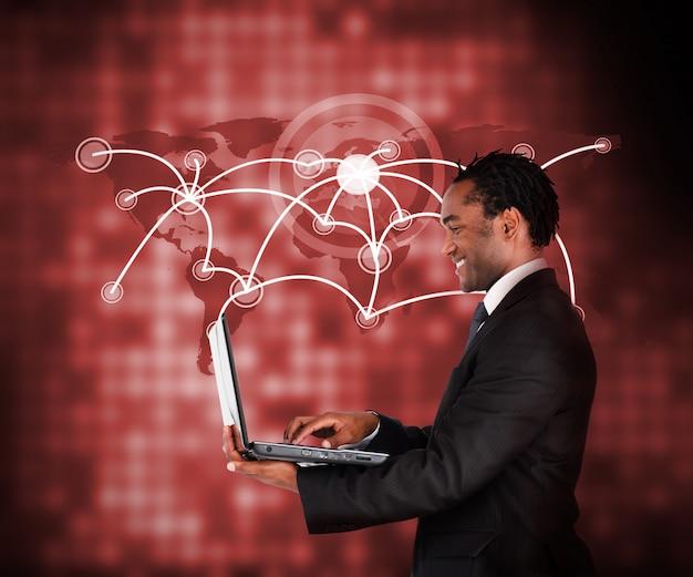 Het glimlachen van laptop van de zakenmanholding tegen een achtergrond