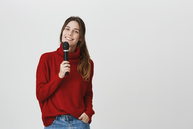 Het glimlachen van leuke vrouw die karaoke zingt, houdt microfoon