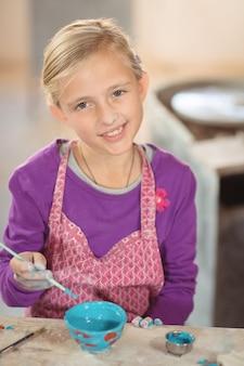 Het glimlachen van meisje het schilderen op kom in aardewerkworkshop