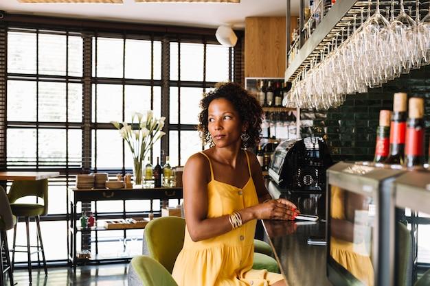 Het glimlachen van modieuze jonge vrouwenzitting bij staafteller die slimme telefoon in het restaurant houden