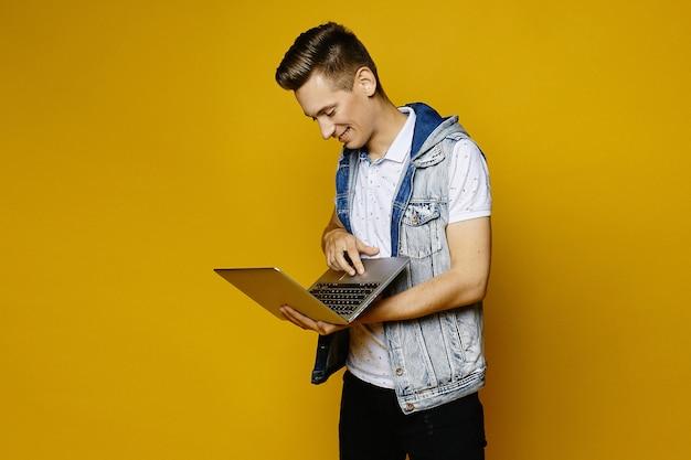 Het glimlachen van modieuze kerel in het toevallige uitrusting stellen met laptop op geeloranje geïsoleerde achtergrond ,. jonge knappe man met laptop in de handen.