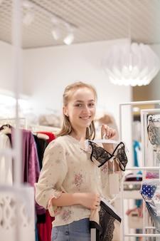 Het glimlachen van mooie brunette die bikini kiezen terwijl status in de winkel. winkelen concept