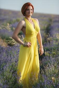 Het glimlachen van mooie brunette op het lavendelgebied bij zonsondergang