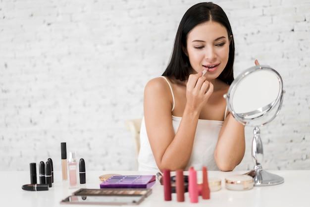 Het glimlachen van mooie vrouwen verse gezonde huid die op spiegel kijken en genieten die thuis lippen met rode lippenstift toepassen. gezichts schoonheid en kosmetisch concept