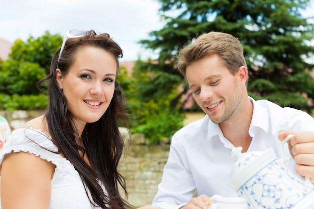 Het glimlachen van paar het drinken koffie in tuin