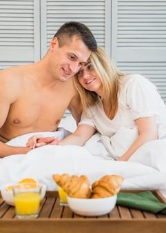 Het glimlachen van paarholding dient bed dichtbij ontbijt aan boord in