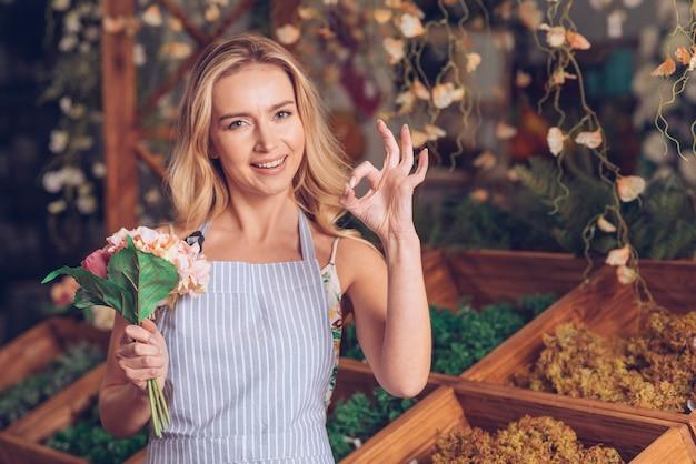 Het glimlachen van portret van een blonde holdingsboeket die van de blonde jong vrouwelijk bloemist in hand ok gebaar maken