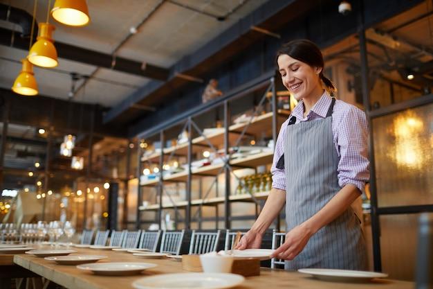 Het glimlachen van serveerster serving table in koffie