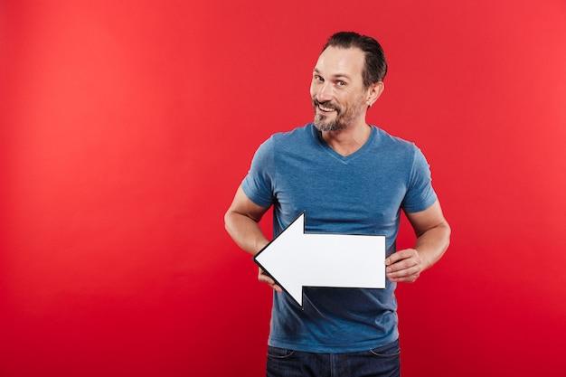 Het glimlachen van volwassen kereljaren '30 die de lege wijzer houden die van de toespraakpijl opzij op copyspace leiden, die over rode achtergrond wordt geïsoleerd