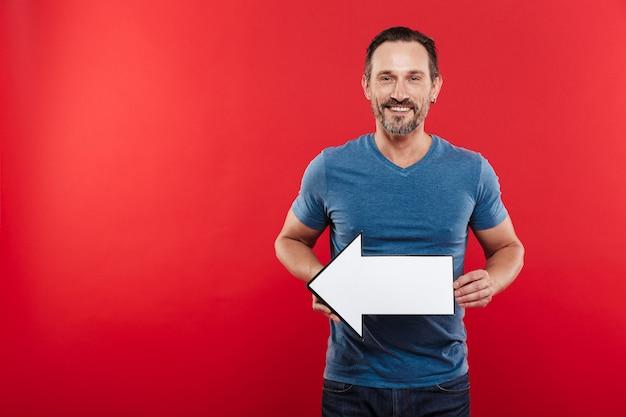 Het glimlachen van volwassen kereljaren '30 die de lege wijzer houden die van de toespraakpijl weg op copyspace leiden, die over rode achtergrond wordt geïsoleerd