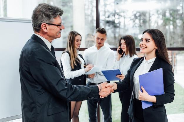 Het glimlachen van vriendschappelijke oudere zakenman het schudden handen met vrouwenverblijf op kantoor.