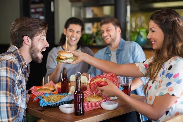 Het glimlachen van vrouwen voedende hamburger aan mannelijke vriend