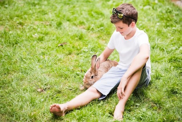 Het glimlachen van weinig jongenszitting met konijn op groen gras