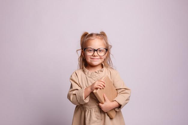 Het glimlachen van weinig schoolmeisjemeisje in glazen met een boek op een grijze achtergrond. plaats voor tekst, banner