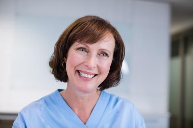 Het glimlachen verpleegsterszitting bij bureau