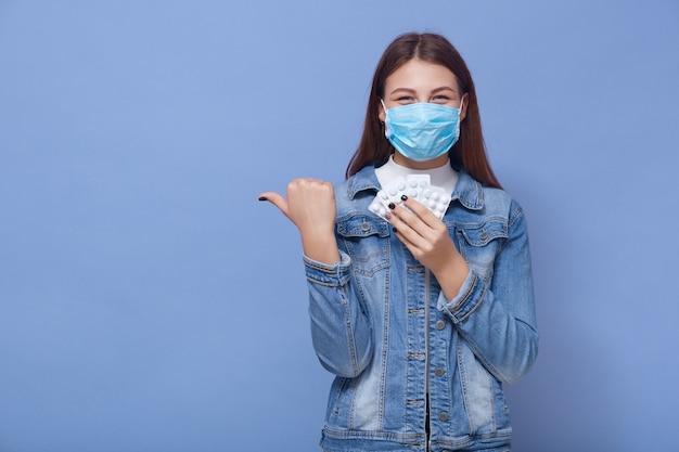 Het glimlachen vrouw stellen geïsoleerd over blauwe muur