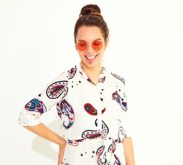 Het glimlachen vrouwenmodel in toevallige de zomerkleren, die haar tong tonen