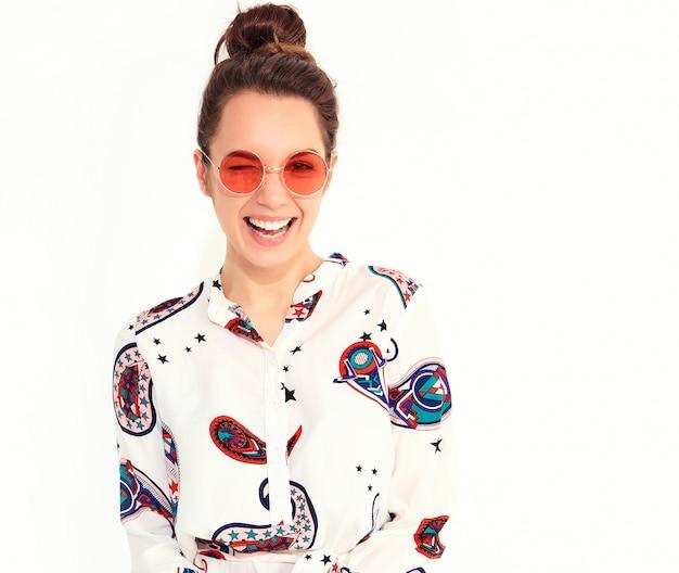 Het glimlachen vrouwenmodel in toevallige de zomerkleren in zonnebril. knipogend