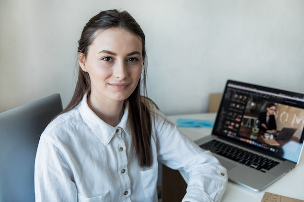 Het glimlachen vrouwenzitting bij haar bureau in bureau. gelukkige bedrijfsvrouwenzitting in bureau met vingers wat betreft haar kin.