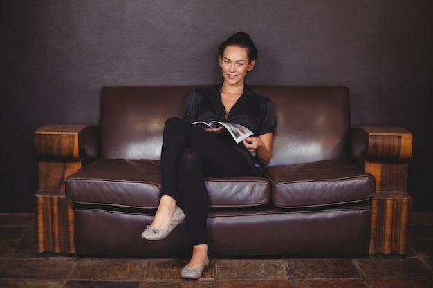 Het glimlachen vrouwenzitting op bank en het lezen van een tijdschrift