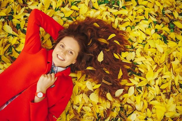 Het glimlachen womn de herfstbladeren in haar