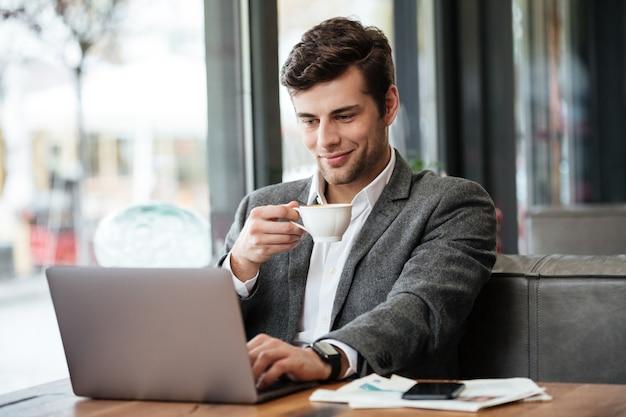 Het glimlachen zakenmanzitting door de lijst in koffie en het gebruiken van laptop computer