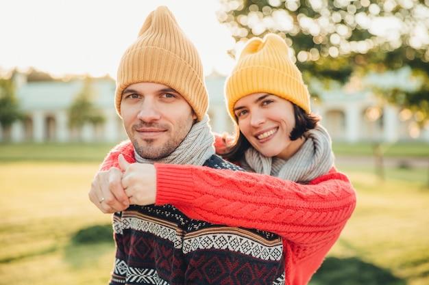 Het glimlachende blije jonge wijfje in hoed en warme katoenen sweater omhelst haar echtgenoot die achteruitgaat