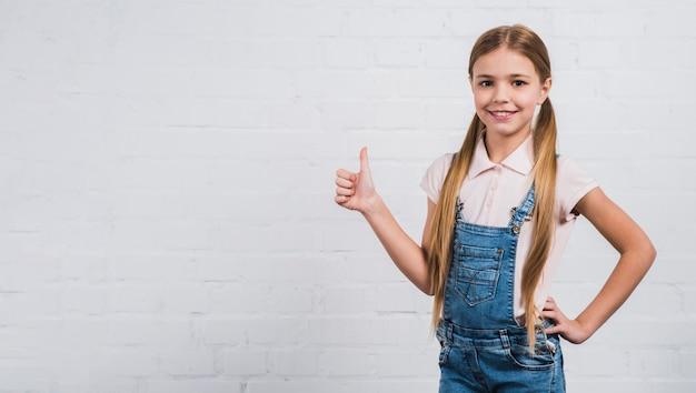 Het glimlachende blondemeisje die duim tonen ondertekent omhoog status tegen witte bakstenen muur