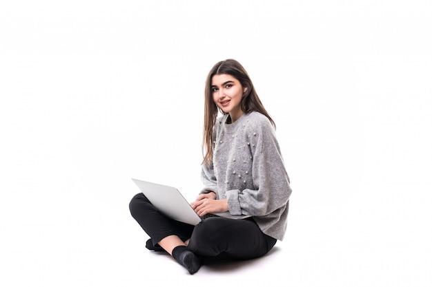Het glimlachende donkerbruine meisjesmodel in grijze sweater zit op de vloer en werkt studie op haar laptop