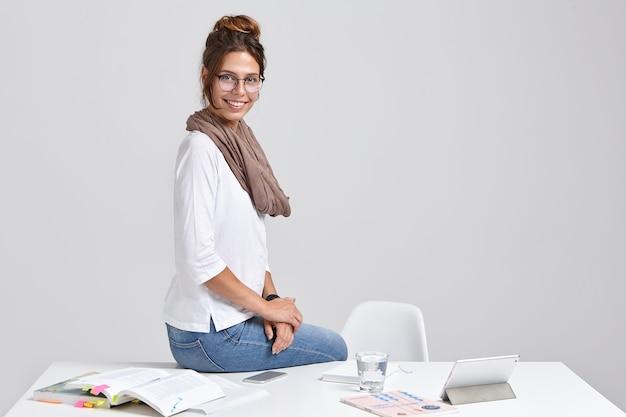 Het glimlachende elegante hipstermeisje zit bij desktop dichtbij tabletcomputer