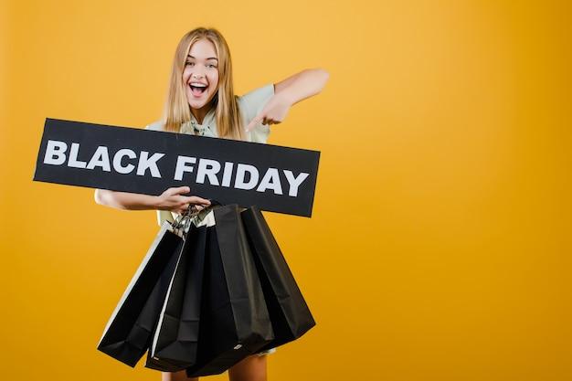 Het glimlachende gelukkige mooie meisje richt vinger op zwart die vrijdagteken met document het winkelen zakken over geel worden geïsoleerd