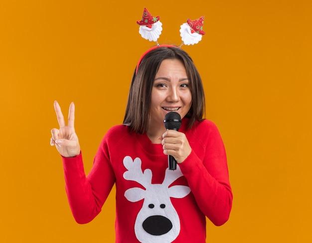 Het glimlachende jonge aziatische meisje die de hoepel van het kerstmishaar met sweater dragen spreekt op microfoon die vredesgebaar toont dat op oranje muur wordt geïsoleerd