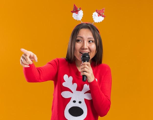 Het glimlachende jonge aziatische meisje die de hoepel van het kerstmishaar met sweater dragen spreekt op microfoonpunten aan kant die op oranje muur wordt geïsoleerd