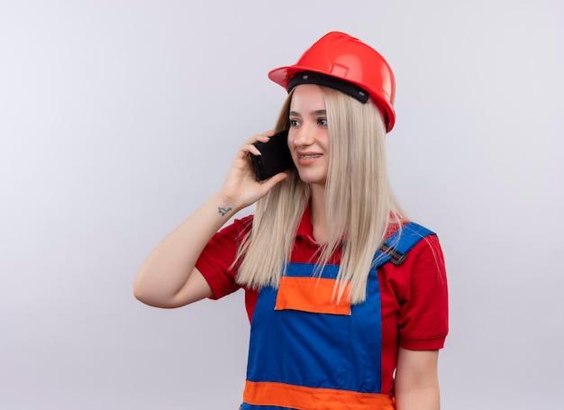 Het glimlachende jonge blonde meisje van de ingenieurbouwer in uniform in tandsteunen die op telefoon spreken die naar linkerkant op geïsoleerde witte ruimte met exemplaarruimte kijken