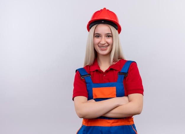 Het glimlachende jonge blonde meisje van de ingenieursbouwer in uniform in tandsteunen die zich met gesloten houding op geïsoleerde witte ruimte met exemplaarruimte bevinden