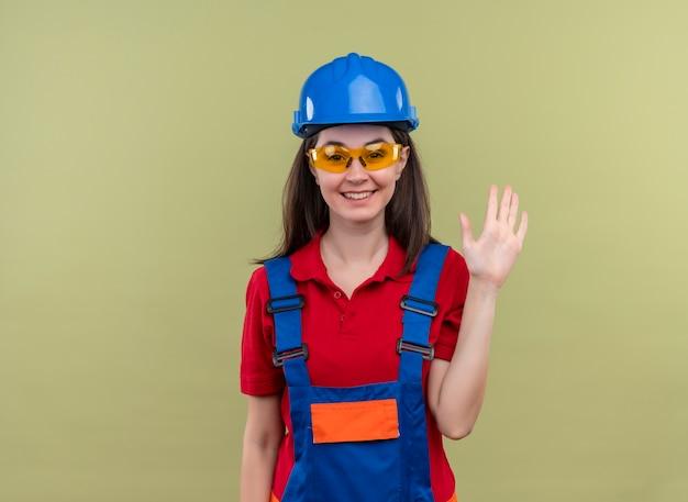 Het glimlachende jonge bouwersmeisje met blauwe veiligheidshelm en met veiligheidsbril houdt hand op geïsoleerde groene achtergrond met exemplaarruimte vast