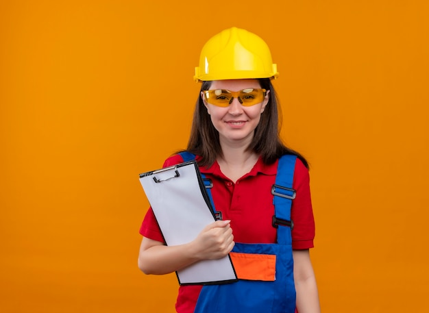 Het glimlachende jonge bouwersmeisje met veiligheidsbril houdt klembord op geïsoleerde oranje achtergrond