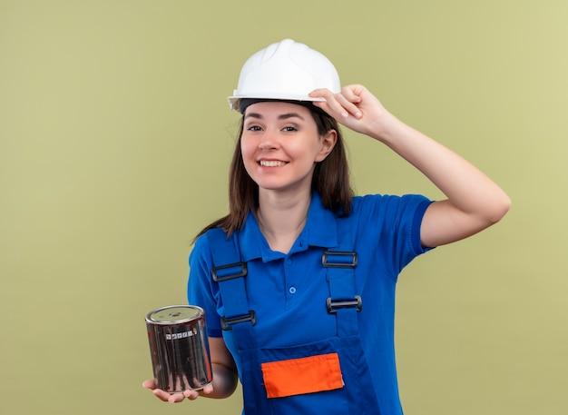 Het glimlachende jonge bouwersmeisje met witte veiligheidshelm en blauw uniform houdt olieverf op geïsoleerde groene achtergrond
