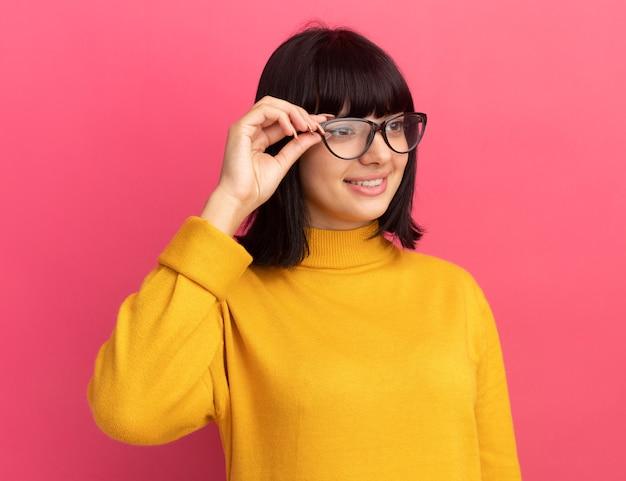 Het glimlachende jonge donkerbruine kaukasische meisje bekijkt kant door optische bril op roze