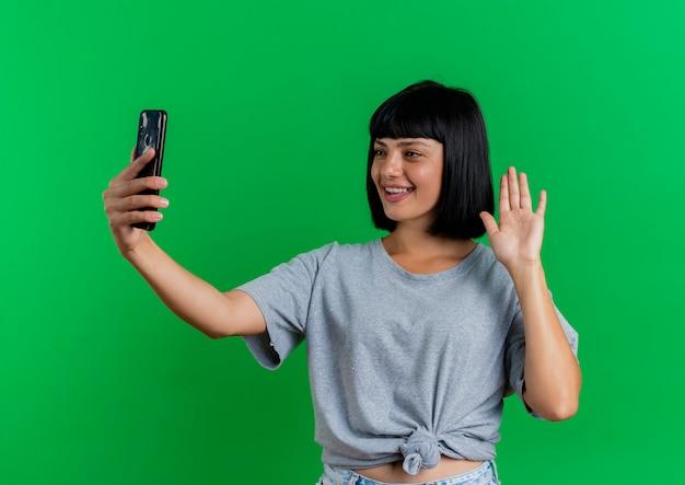 Het glimlachende jonge donkerbruine kaukasische meisje heft hand op en bekijkt telefoon die op groene achtergrond met exemplaarruimte wordt geïsoleerd