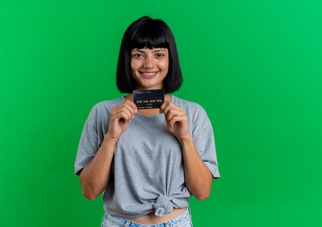 Het glimlachende jonge donkerbruine kaukasische meisje houdt creditcard die camera bekijkt die op groene achtergrond met exemplaarruimte wordt geïsoleerd